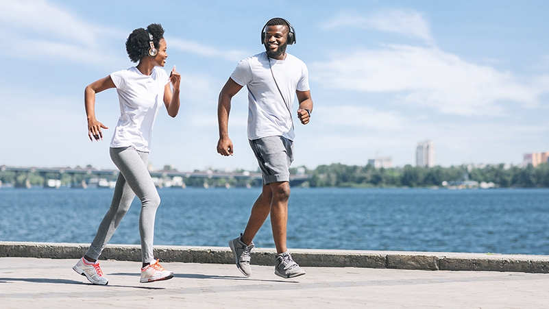 Young African American Man and Woman jogging near water