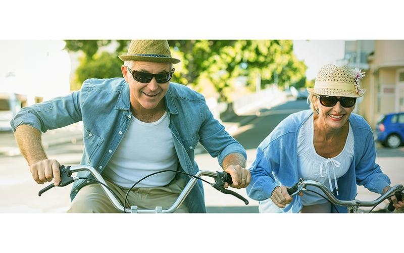 older couple riding bikes, enjoying Total Body Wellness